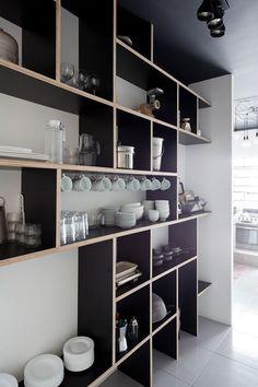 Pequeña cocina donde el hormigón y el tablero marino en negro, junto con los azulejos blancos encintados en negro también, conv...