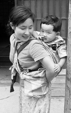 1956(昭和31年)頃の夏。おんぶが慣れない様子の、まだ若いお母さん。                                                                                                                                                                                 もっと見る