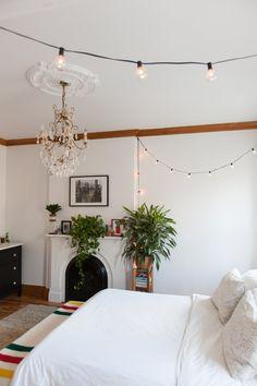 The bedroom effortlessly blends old chandelier charm with string lights.