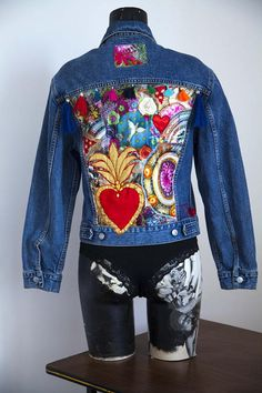 Table made of fabric applications using BORO, tassels, satin flowers, pearls in the back. Ex-voto, Dove. And at the top under the collar label cut in a fabric very colorful. Front, two pockets at the top. No custom. Quality denim fabric. Free shipping in France. Found in thrift, and
