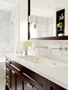 walnut cabinets, marble, quartz countertops???, sconces in mirror, faucets coming out of wall, glass shower door