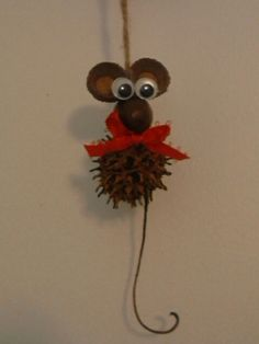 Homemade christmas ornament made from sweet gum pod, acorn for nose and acorn tops as ears added bow and googley eyes hung with twine