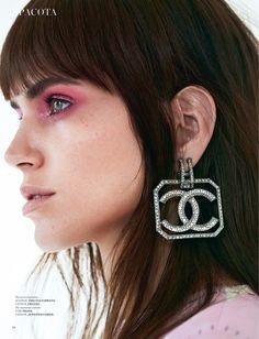 Wearing pink eyeshadow, Amanda Wellsh models Dolce & Gabbana dress with Chanel logo earrings