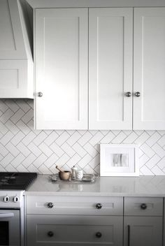 A classic and chic herringbone pattern in white subway tiles as the kitchen backsplash with white marble countertops and white cabinets with chrome hardware. Description from pinterest.com. I searched for this on bing.com/images
