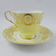 Paragon tea cup and saucer, yellow with gold decoration. Fruit and flowers on inside rim of tea cup and in center of saucer. Gold trimming and ribbing on teacup and saucer. Excellent condition (see photos). Paragon started as the Star China Company in 1897, founded by Hugh Irving and
