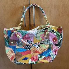 Laminated Patchwork Handbag Why blend in, when you can stand out! This bag is so pretty! A definite conversation piece. Just picture how awesome it would look with a black top, skinny jeans and black heels! Sounds like a showstopping combo to me!! Colorful, vibrant, and roomy, this bag has a gold interior and braided handles. Magnetic closure and zipper compartment inside. I do not have the strap. Used once, excellent condition. Braciano Bags