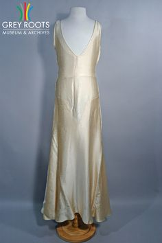 A sleeveless, cream-coloured, floor-length satin evening gown with distinctly 1920s styling. The dress would have been worn with a matching belt (not pictured). Grey Roots Museum & Archives Collection.
