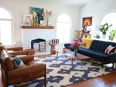 what a great living room! amazing sofa, chairs, carpet, plants, and decor....