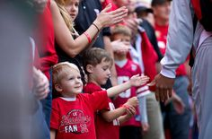 Sam Schlautman, 3, of Lincoln reaches out for high fives from Nebraska football players as they enter Memorial Stadium in Lincoln, Neb., Saturday, September 29, 2012.  By: REBECCA S. GRATZ/THE WORLD-HERALD