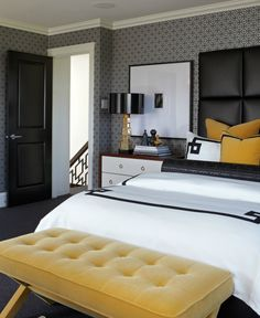 Atmosphere Interior Design Contemporary yellow & black bedroom design with black & white geometric pattern wallpaper, black leather padded headboard, white hotel bedding with black Greek key trim, yellow velvet pillows, black leather Greek key bolster pillow, yellow velvet tufted bench, gold mirrored lamps with black vinyl shades and modern nightstands with ring pulls.