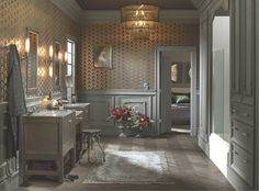 Here in this Victorian-inspired bathroom, smoky grays and dusty browns are paired with a metallic wallcovering and warm bronze light fixtures, giving a glow that radiates through an already welcoming room.