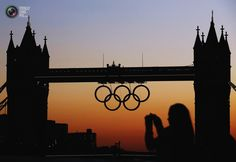 A woman photographs the Olympic rings positioned on Tower Bridge for the 2012 London Olympic Games. LUKE MACGREGOR/REUTERS