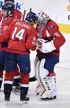 Washington Capitals right wing Justin Williams (14) celebrates a win over the Philadelphia Flyers with goalie Philipp Grubauer (31), of Germany, after an NHL hockey game, Sunday, Jan. 15, 2017, in Washington. (AP Photo/Nick Wass)