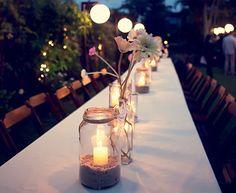 Velas acomodadas em garrafas e potes produzidos por Juliana von Ostau iluminaram a mesa de jantar deste casamento