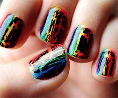 Rainbow stripe manicure with black crackle polish over it.