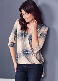 A contemporary twist on a classic check shirt. Featuring a gorgeously feminine coloured check, in flattering wrap styling, with a collar, a hemline which i