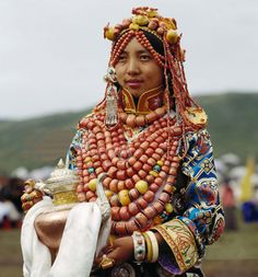 Gannan Tibetan wears her family's collection of heirloom items at a festival in Amdo - if real, her jewelry is very valuable indeed. Nomadic Tibetans use ornaments as a store of wealth, because it is easily transportable, and can be handed down through the generations