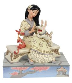 """Mulan is breathtaking, sitting on a bench in her best dress. With her excitable pup, Little Brother, bouncing in her lap and her dragon guardian Mushu in a tight hug, she's surrounded by love. Beautifully sculpted, this Jim Shore piece is a classic.Introduced January 2020FigurineApprox. 5.5""""Imported."""