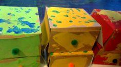 """Pattiseriedoosjes versiert: eerst verven met verfrol, daarna met vingerverf stipjes maken. Een """"belletje"""" op de voorkant. In het doosje zit een foto van de kinderen met het versje bij: Doosje, doosje, ga eens open, want ik kom er in gekropen, klepjes die gaan toe, oma opa druk eens op het belletje...DING DONG....KIEKEBOE! Er lagen ook zelfgemaakte koekjes van de peuters in de doos.  (thema dozen + grootouders gemixt)"""