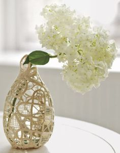 Tightly wrap a doily around a vase. Snip away any excess, then hand-stitch the doily securely in place to create a snug fit. A clear glass vase creates an elegant illusion, but experiment with different vases and doilies to find a combination you like.  Plus: More ideas for decorating with vintage doilies »