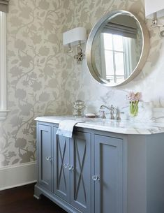 Silver and gray powder room features walls clad in white and silver wallpaper lined with a gray washstand fitted with x mullion cabinet doors adorned with glass knobs paired with a white marble countertop and a curved marble backsplash under a silver convex mirror illuminated by 2 light wall sconces.