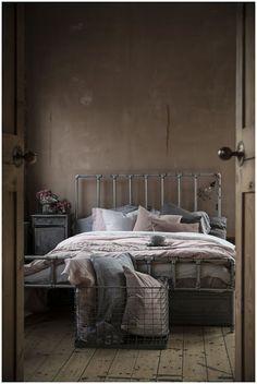 #Dormitorio con mucho estilo dominado por las piezas metálicas y la crudeza del resto de materiales, tanto en el suelo como en la pared, rematado todo por el detalle de la lampara cogida al cabecero que nos encanta.