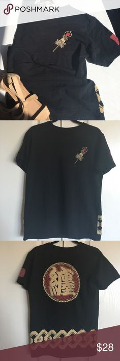 """Straight from Japan 🇯🇵 Black Tshirt This fantastic item was imported straight from Japan.  As you can see, there is a ton of detail from the symbol on the chest and one on the sleeve as well as a yoked back, border and large symbol in tan and red. Not sure what it says but I'd guess it says """"I'm beautiful"""" or """"Have a wonderful day"""" or """"I'm a sexy beast!"""" 😂. T is NWT, has cute detailing inside the shirt and is size L   Bust 20"""" length 25.5"""" hips 18""""   Arigato🇯🇵😀 Tops Tees - Short Sleeve"""
