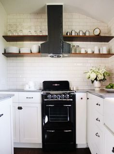 The stained wood shelving framing the steel hood in this small kitchen, designed by Amy Sklar, is a genius use of space. And that black vintage-inspired stove might be the cutest little appliance ever.
