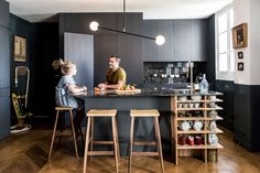 Black cabinetry and island in moody kitchen with wood stools, modern light fixture, and wood shelving