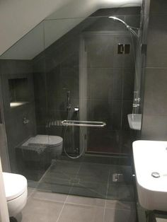 Frameless shower enclosure in Clapham, designed discretely to allow use by client with restricted mobility.