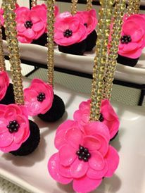 Pink flowers on black cake pop with gold sticks.