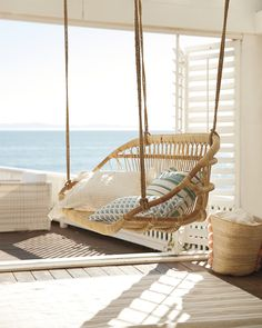 Serena & Lily Hanging Rattan Bench This relaxing rattan bench makes you feel beach-side. Its Scandinavian design gives a coastal air, and a set of throw pillows makes it undeniably inviting.