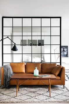There is a balance in the contrasting reddish ocra brown couch and the minimalistic feeling of the room