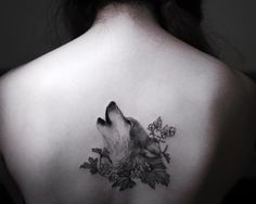 wolf and floral elements tattoo on the back for women