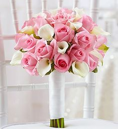 PINK & WHITE BRIDAL BOUQUET :: The beauty of pink roses and spectacular white Calla lilies accented with variegated pittosporum creates an aura of sophisticated elegance. Finished with a crisp white ribbon, this lovely bridal bouquet is a true original.