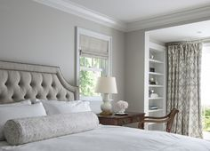 Traditional master bedroom features light gray walls framing a gray tufted velvet bed dressed in soft white bedding and gray damask bolster pillow beside an antique bed as nightstand topped with a white double gourd lamp, Small Form Gourd Lamp, paired with antique chair situated under window covered in gray roman shade, beside built in bookcase in front of window adorned with, gray trellis curtains in Braemore Fioretto Sprout Fabric.