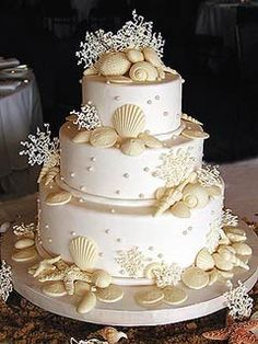 Three tier ivory wedding cake decorated with white chocolate seashells, ivory coloured edible sea coral and cream coloured pearls. From www.justfab.com