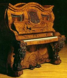 The Napoleon Hat Shape Piano : : one of the earliest surviving upright pianos, was commissioned by Queen Victoria in 1853, and made in England as a wedding gift for Napoleon III, a nephew of Napoleon Bonaparte. Made of walnut wood, the piano has beautifully carved decorations of roses and figs on its legs and pedals : : Museum of Musical Instruments in Ekoda, Tokyo (Japan)