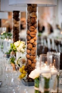 Nuts inside a tall cylinder vase can add a rustic touch to the centerpiece.