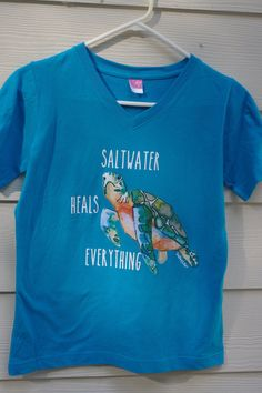 Now in V neck and Turquoise color.  Isnt this quote so true? Saltwater heals everything. And everyone loves sea turtles. What better combination. This tshirt is a new design in our Shelling Life® collection. This tshirt is white with beautiful and vibrant shades of aqua, turquoise and coral. Youre going to love this tshirt!  These shirts are 100% combed cotton and super soft! They have not been preshrunk. They have a V neck and short sleeves for comfort and side seam with missy contoured…