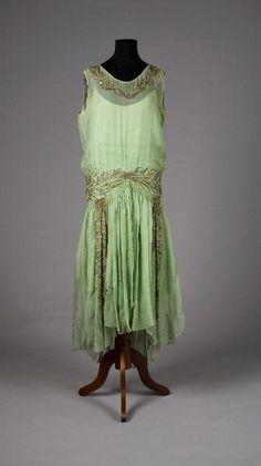 MM 023660 :: klänning m. underklänning, 1927 Klänning med lös underklänning av ljusgrön silkescrêpe, garnerad med broderier av pärlor och paljetter i stål, silver och guld. Rund halsringning. Ärmlös. Kjollängden kortare fram. Foder av ljusgrönt siden, s k crêpe de chine. Märkt: Maguet PARIS 11. Place de la Madeleine
