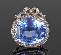Exceedingly fine Faberge brooch, workmaster August Hollming, the 28.19 carat cushion-cut Ceylon sapphire, surrounded by sixty-eight rose cut diamonds with ribbon top.