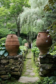 Incredibly charming garden in Connecticut with dry laid stone walls, cobblestone paths, and these large vessels.