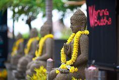 Beautiful Buddha statues bedecked in yellow flowers, Bali, Indonesia