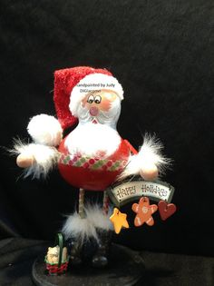 The Santa gourd is perched on top of skinny legs decorated with green and red dots that match his belt. He is holding a Seasons Greeting
