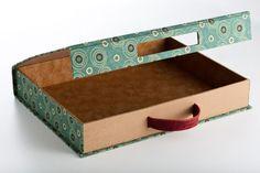 Caixa rígida confeccionada em papelão neutro, revestida em tecido e alça em couro.
