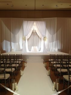 Wedding ceremony with white chuppah and white florals.