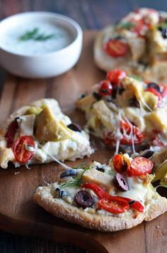 """Loaded Greek Chicken """"Pitzas"""".  These pita bread pizzas are topped with tzatziki, chicken breast, 3 cheeses, artichokes, olives, roasted red peppers, and tomatoes.     hostthetoast.com"""