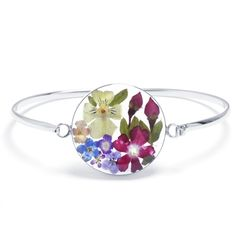 Stack our bangle bracelet with everyday jewelry for a trendy look or wear it on its own for a chic statement. The bangle showcases an oval center featuring multiple real pressed dried flowers including miniature Roses, Forget Me Nots, Amaryllises, Lantana Camaras, Verbenas and Sweet Alyssums preserved in top-quality clear resin and encased in rhodium plated sterling silver. Grown in the fields of Taxco, Mexico, these miniature flowers are gathered by hand and forever preserved to be worn…