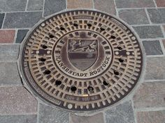 The manhole covers in Rostock display the coat of arms of the city. The coat of arms dating back to 1367 depicts a golden griffin of a blue field (representing the former princes of Rostock) with bars of silver and … Continue reading → Saxony Anhalt, Rhineland Palatinate, Lower Saxony, North Rhine Westphalia, Coat Of Arms, Cover Art, Tapas, Germany, Colours